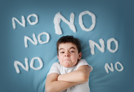 52382220 - bad boy on blue blanket background. angry child with no words around